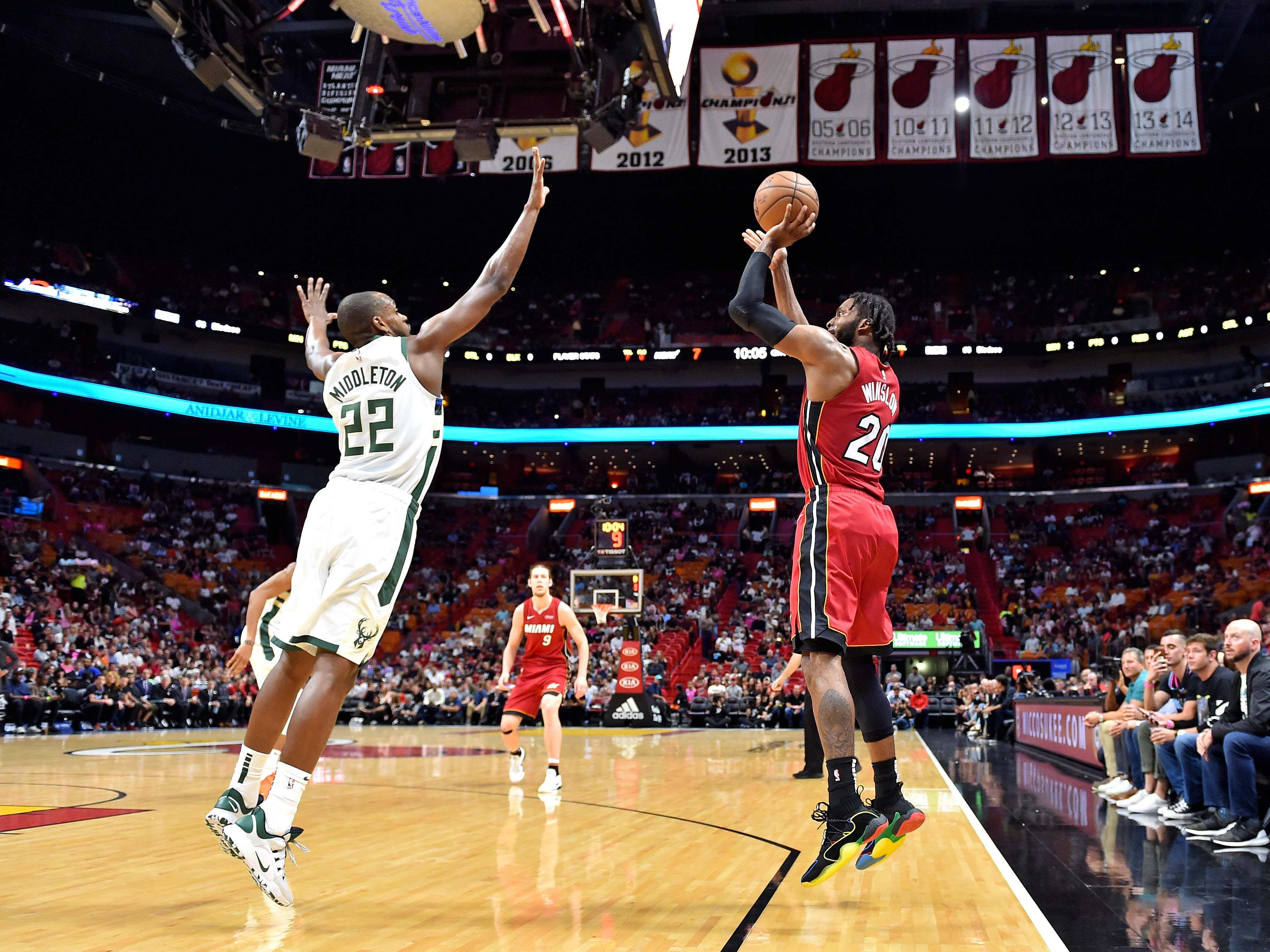 Miami Heat forward Justise Winslow makes a three-pointer over Khris Middleton in the first half.