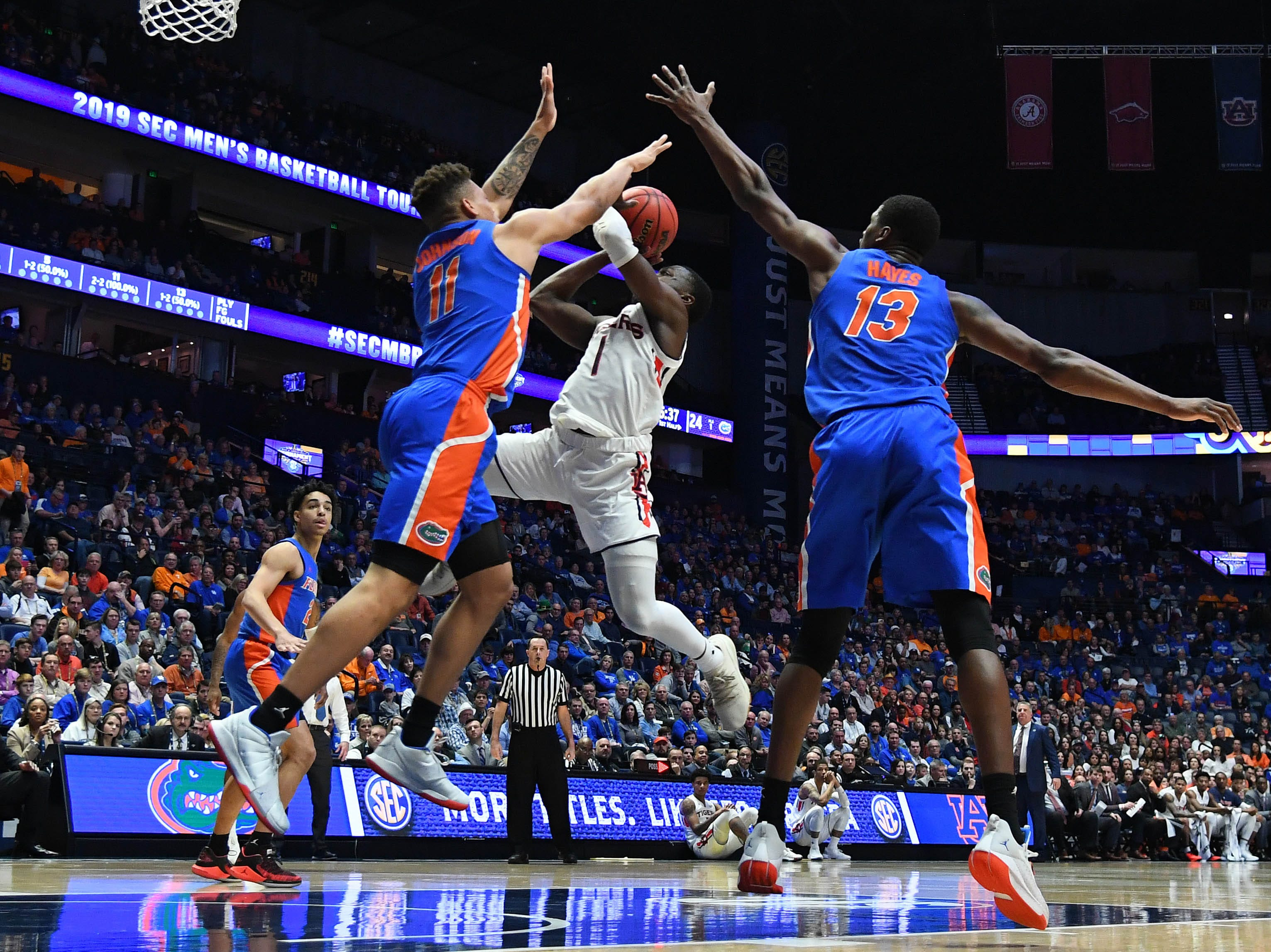 Mar 16, 2019; Nashville, TN, USA; Auburn Tigers guard Jared Harper (1) attempts a shot in the lane against Florida Gators forward Keyontae Johnson (11) and Florida Gators center Kevarrius Hayes (13) during the first half of the SEC conference tournament at Bridgestone Arena. Mandatory Credit: Christopher Hanewinckel-USA TODAY Sports