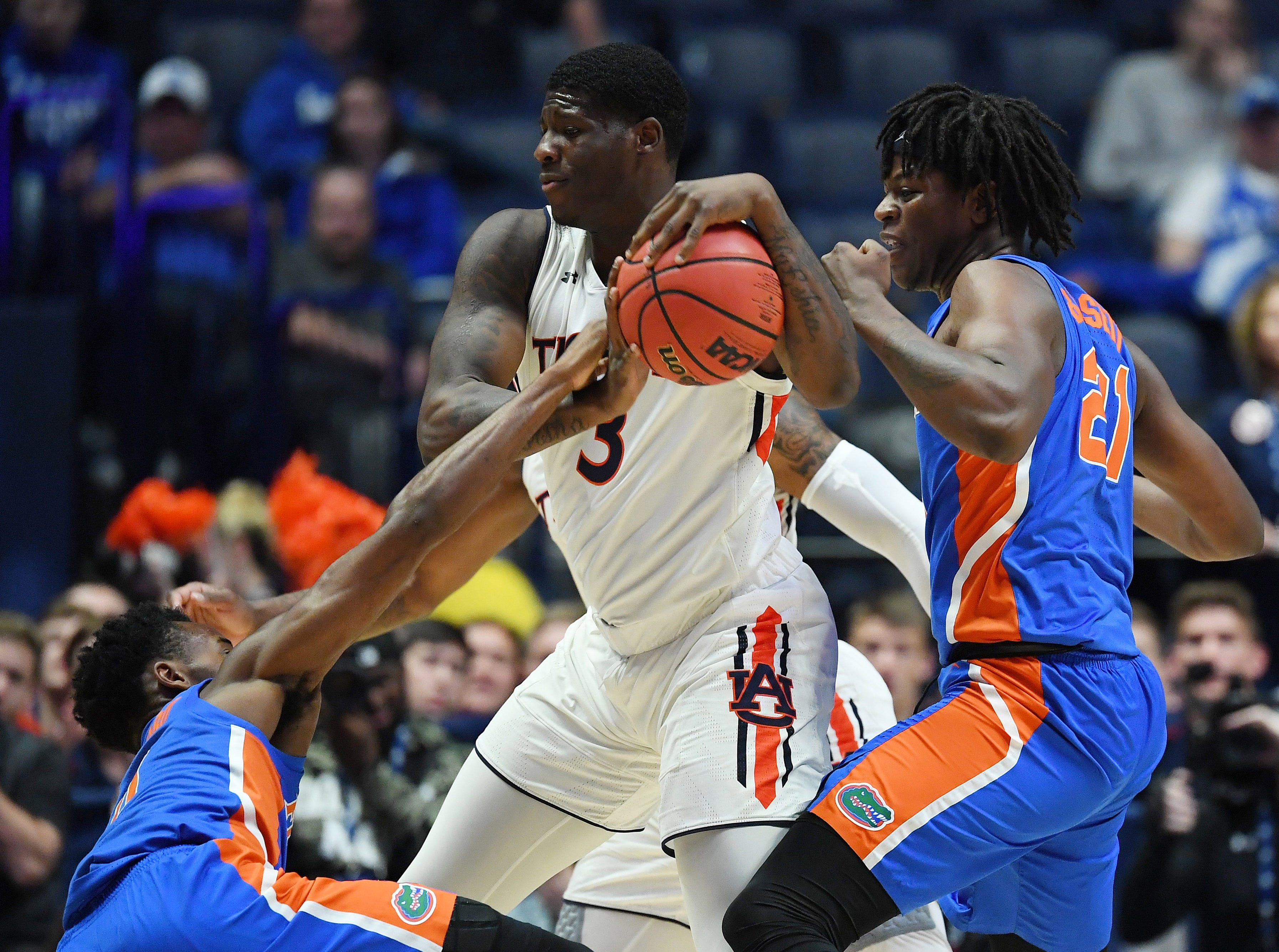 Mar 16, 2019; Nashville, TN, USA; Auburn Tigers forward Danjel Purifoy (3) controls the ball between Florida Gators guard Mike Okauru (0) and Gators forward Dontay Bassett (21) during the first half of the SEC conference tournament at Bridgestone Arena. Mandatory Credit: Christopher Hanewinckel-USA TODAY Sports