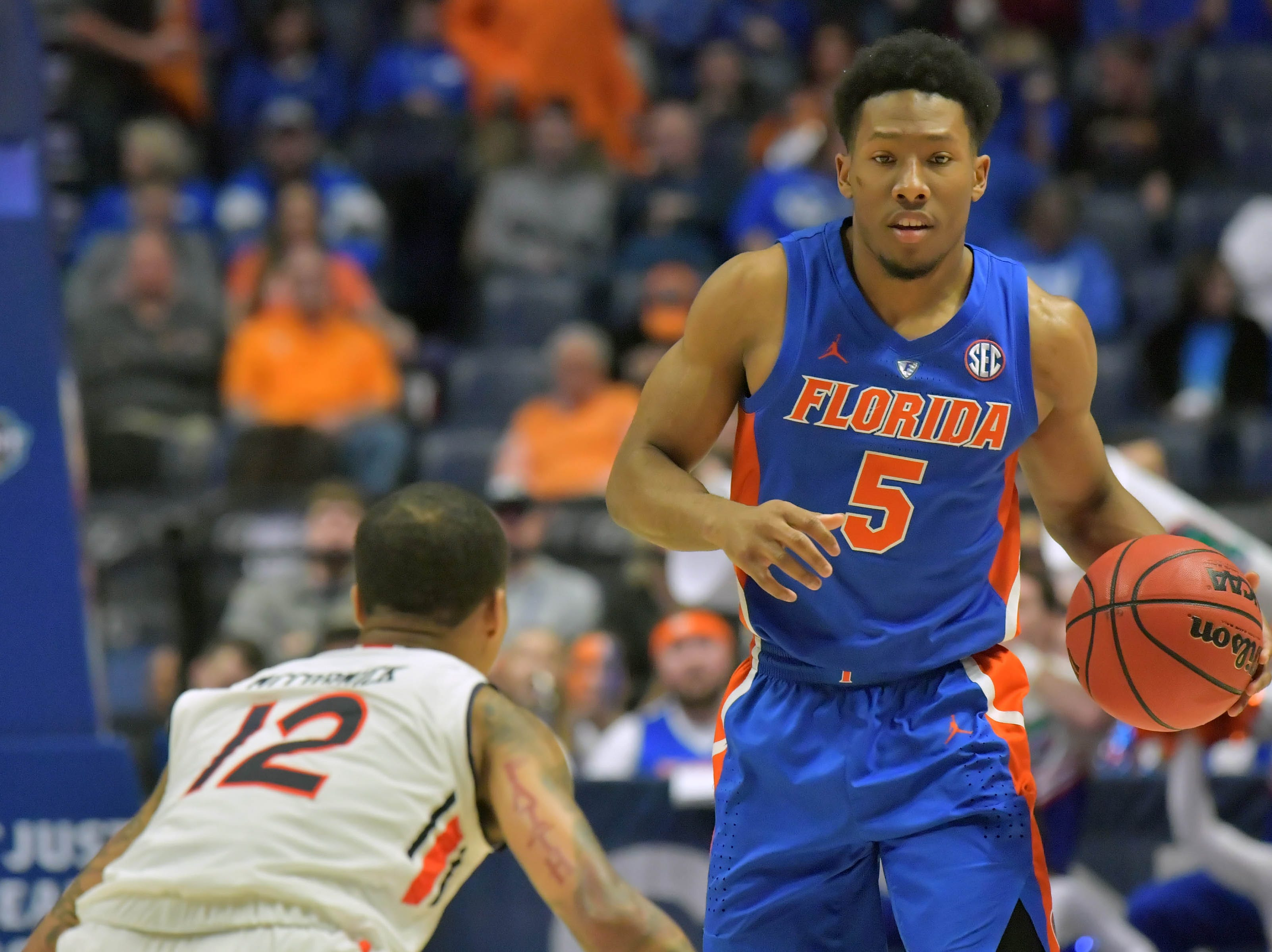 Mar 16, 2019; Nashville, TN, USA; Florida Gators guard KeVaughn Allen (5) controls the ball against Auburn Tigers guard J'Von McCormick (12) during the first half of game eleven in the SEC conference tournament at Bridgestone Arena. Mandatory Credit: Jim Brown-USA TODAY Sports