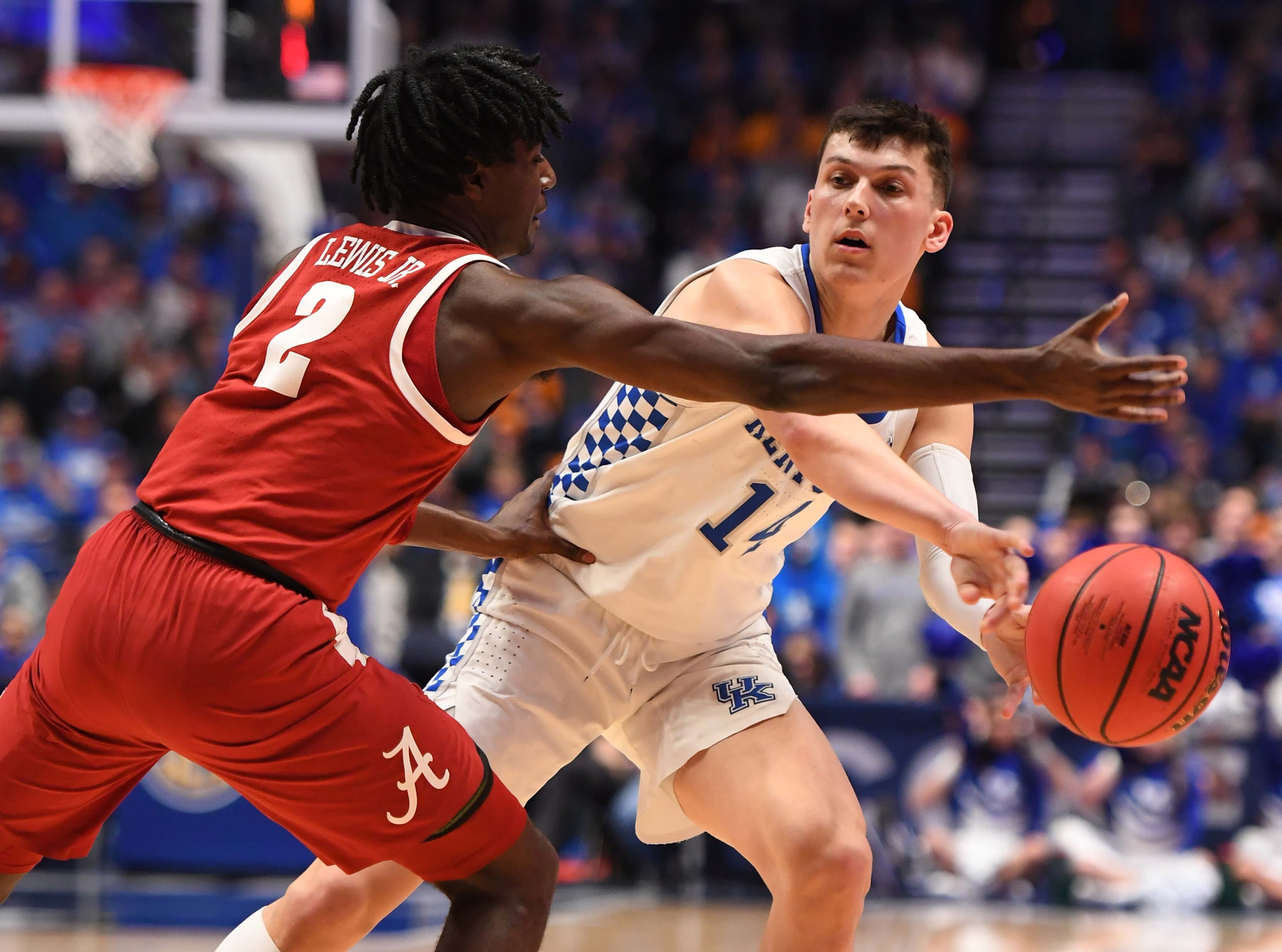 Mar 15, 2019; Nashville, TN, USA; Kentucky Wildcats guard Tyler Herro (14) passes around Alabama Crimson Tide guard Kira Lewis Jr. (2) during the first half of the SEC conference tournament at Bridgestone Arena. Mandatory Credit: Christopher Hanewinckel-USA TODAY Sports