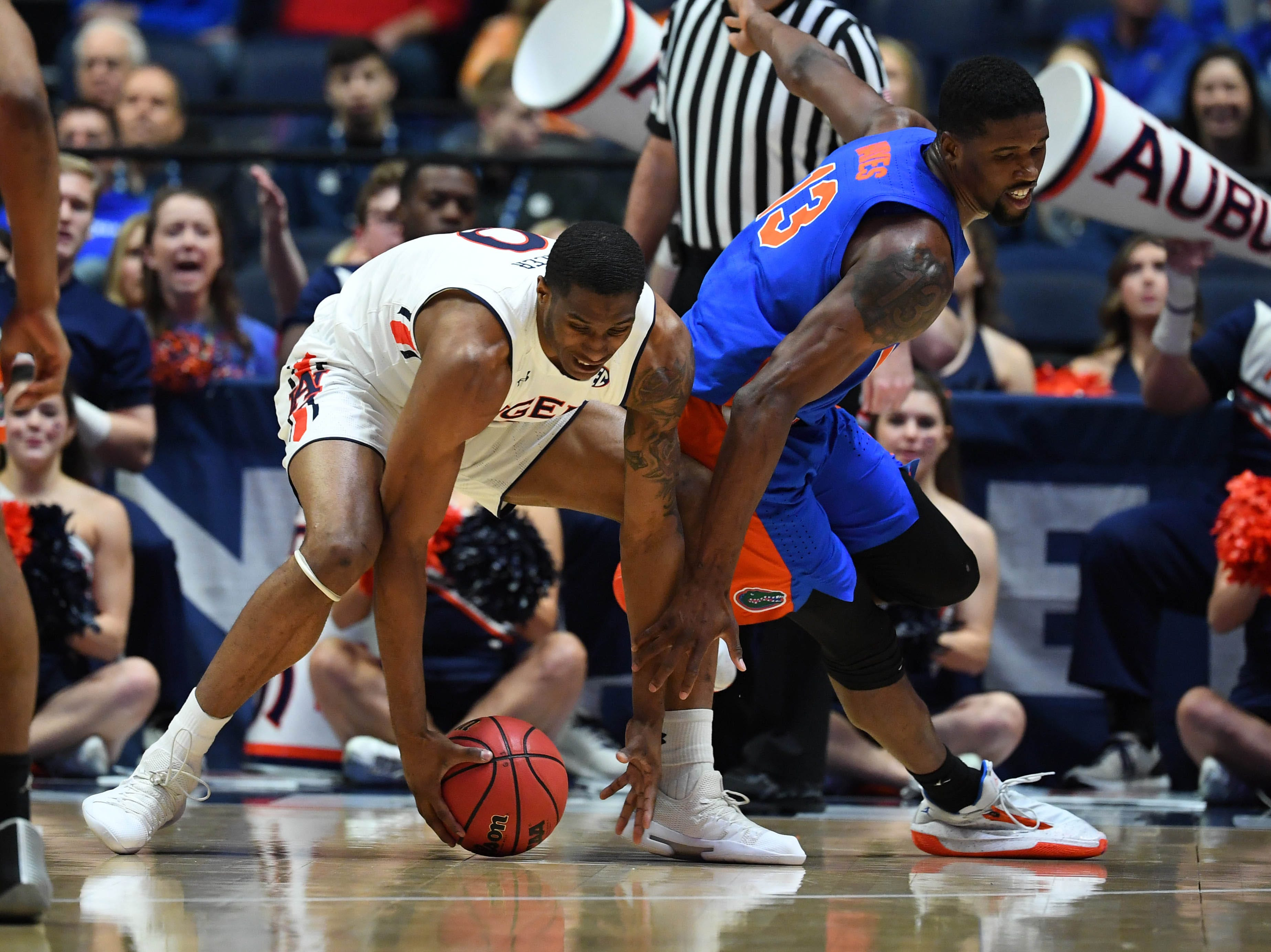 Mar 16, 2019; Nashville, TN, USA; Florida Gators center Kevarrius Hayes (13) tries to chase down a loose ball against Auburn Tigers forward Horace Spencer (0) during the first half of the SEC conference tournament at Bridgestone Arena. Mandatory Credit: Christopher Hanewinckel-USA TODAY Sports