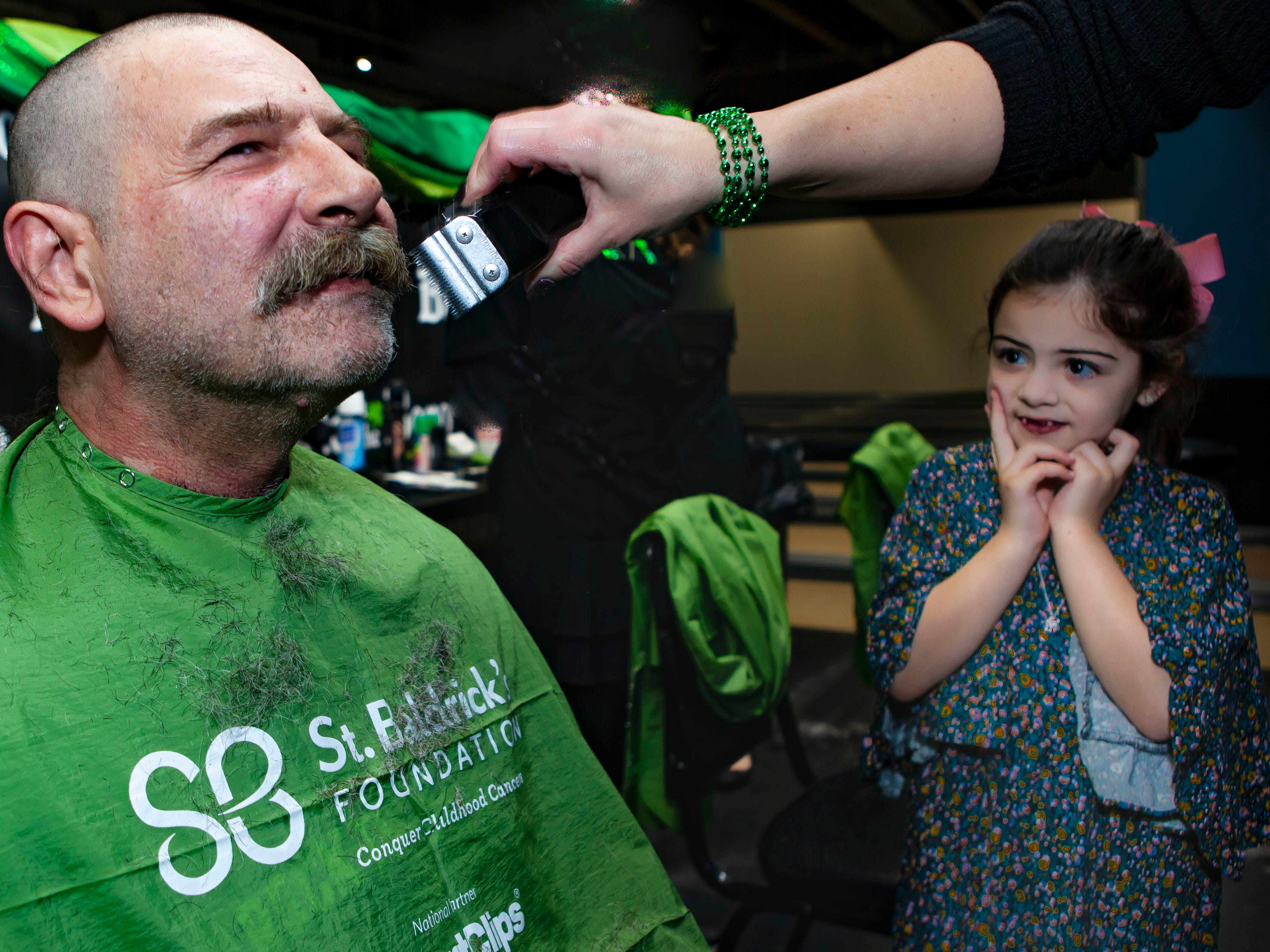 Sadie Smith, one of the children honored at the ninth annual Bald in the Boro, watches as Tracy Terral finishes his turn in the chair. Smith fought cancer at age 3 and is a kindergarten student at Buchanan Elementary. The St. Baldrick's Foundation fundraiser was held Friday, March 15, 2019 at Lanes, Trains and Automobiles in Murfreesboro.