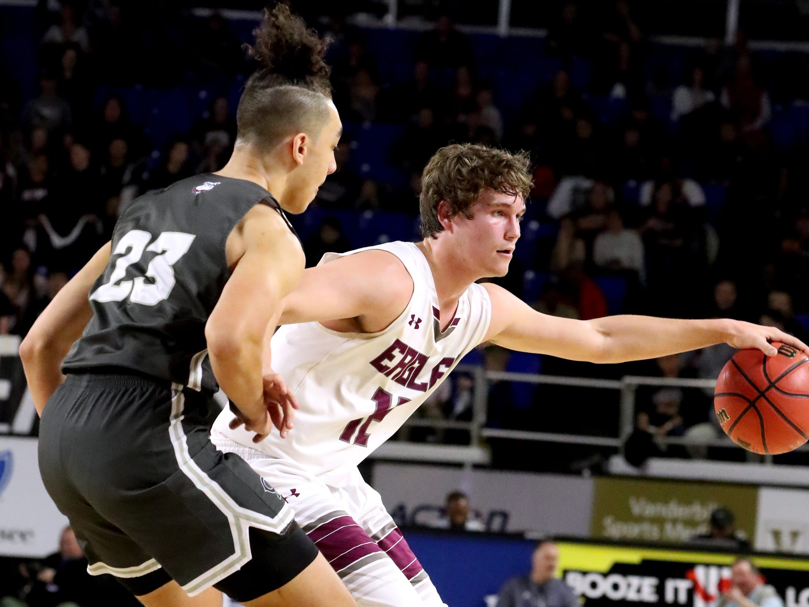 Eagleville's Ethan Cobb (12) moves the ball around he court as Columbia Academy's Gary Smith, Jr. (23) guards him during the semifinal round of the TSSAA Class A Boys State Tournament, on Thursday, March 15, 2019, at Murphy Center in Murfreesboro, Tenn.