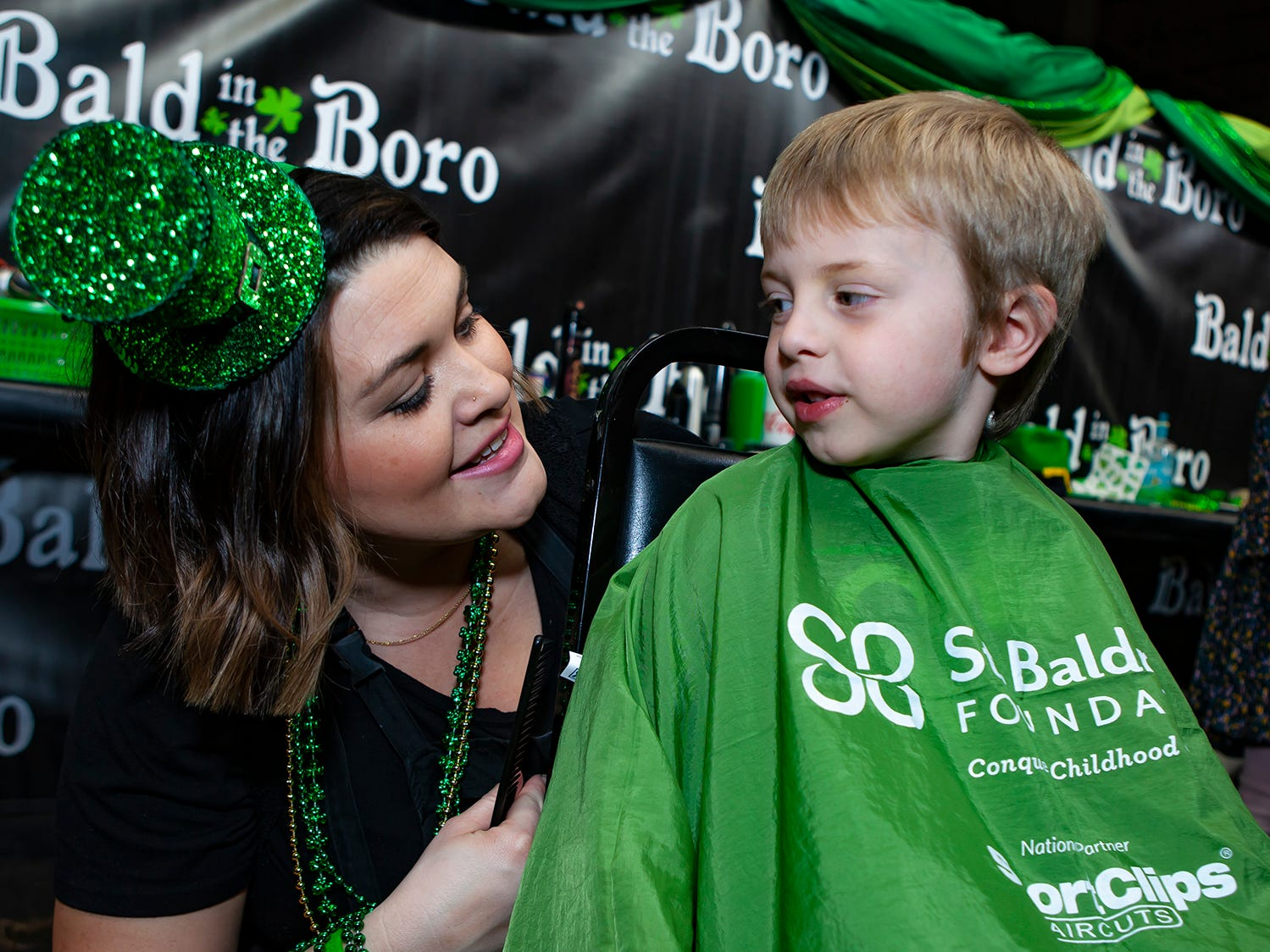 Brittnie Bern with Beehive salon chats with a boy before cutting his hair at the ninth annual Bald in the Boro fundraiser, held Friday, March 15, 2019 at Lanes, Trains and Automobiles in Murfreesboro.