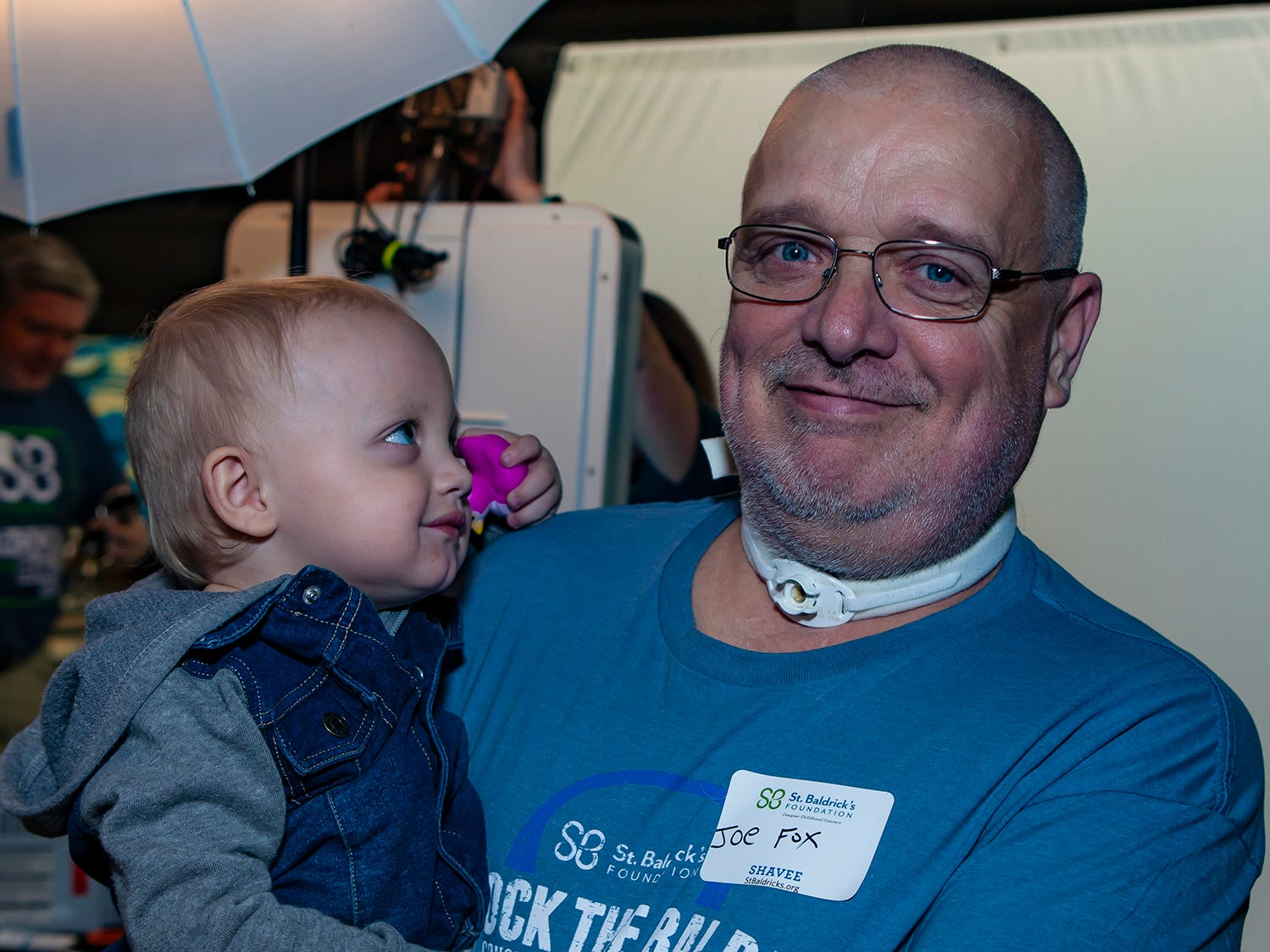 Bralynn Fox, 16  months, takes in granfdather Joe Fox's new look at the ninth annual Bald in the Boro fundraiser for the St. Baldrick's Foundation. The event was held Friday, March 15, 2019 at Lanes, Trains and Automobiles in Murfreesboro.