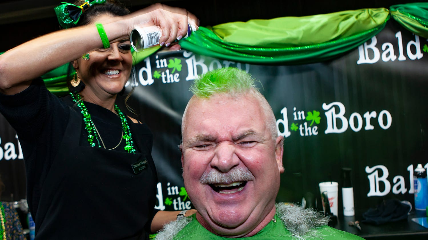 Darlene Skaggs gives Chris England a green mohawk at the ninth annual Bald in the Boro fundraiser for the St. Baldrick's Foundation. The event was held Friday, March 15, 2019 at Lanes, Trains and Automobiles in Murfreesboro.