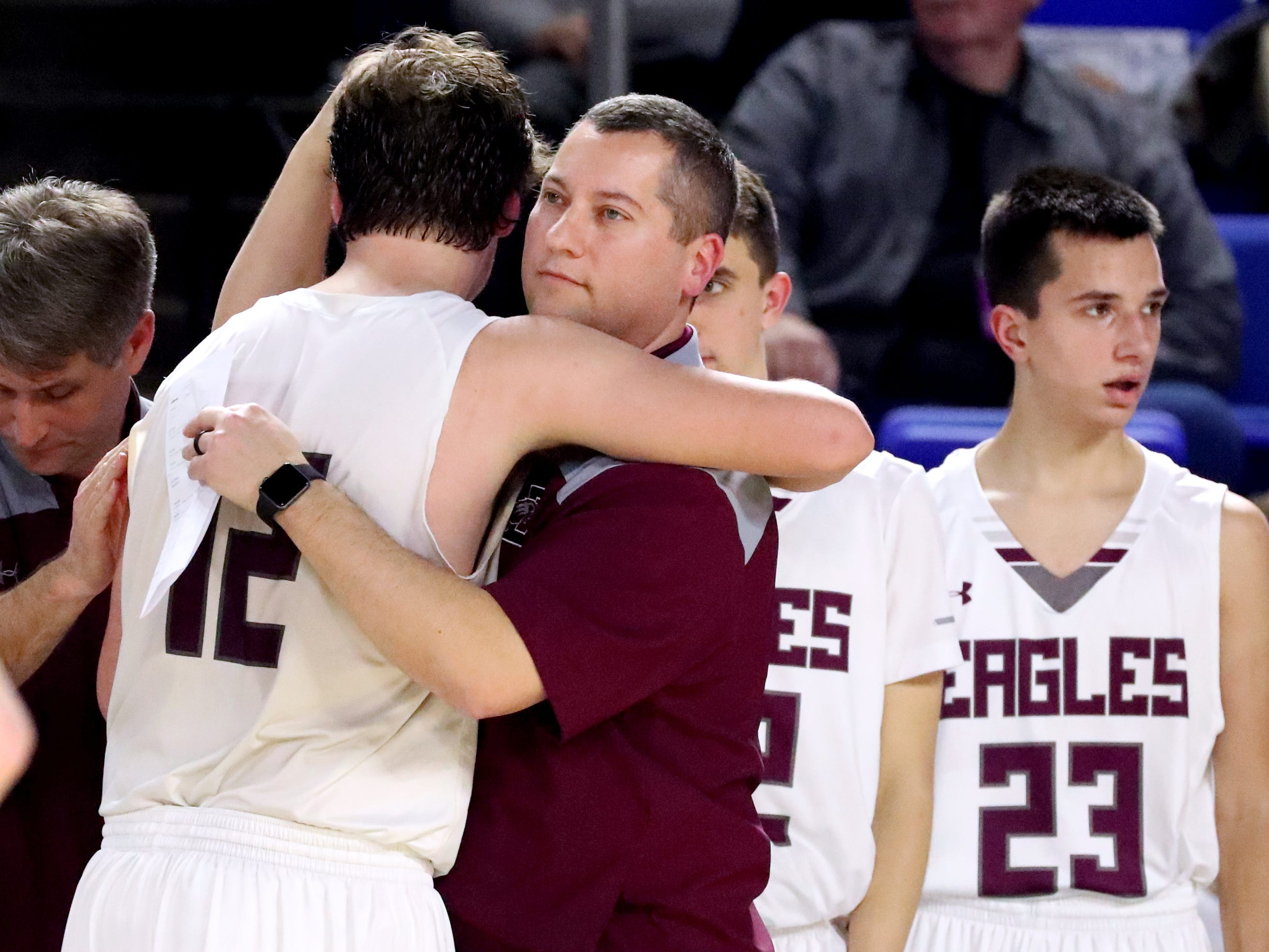 Eagleville's head coach Davy McClaran hugs senior Eagleville's Ethan Cobb (12) as he comes out of the game as they lose to Columbia Academy during the semifinal round of the TSSAA Class A Boys State Tournament, on Thursday, March 15, 2019, at Murphy Center in Murfreesboro, Tenn.