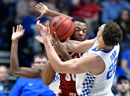 Alabama forward Galin Smith (30) and Kentucky forward Reid Travis (22) battle for the ball during the first half of the SEC Men's Basketball Tournament game at Bridgestone Arena in Nashville, Tenn., Friday, March 15, 2019.