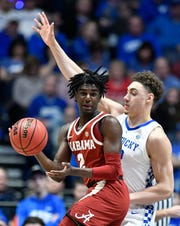 Alabama guard Kira Lewis Jr. (2) moves the ball defended by Kentucky forward Reid Travis (22) during the first half of the SEC Men's Basketball Tournament game at Bridgestone Arena in Nashville, Tenn., Friday, March 15, 2019.