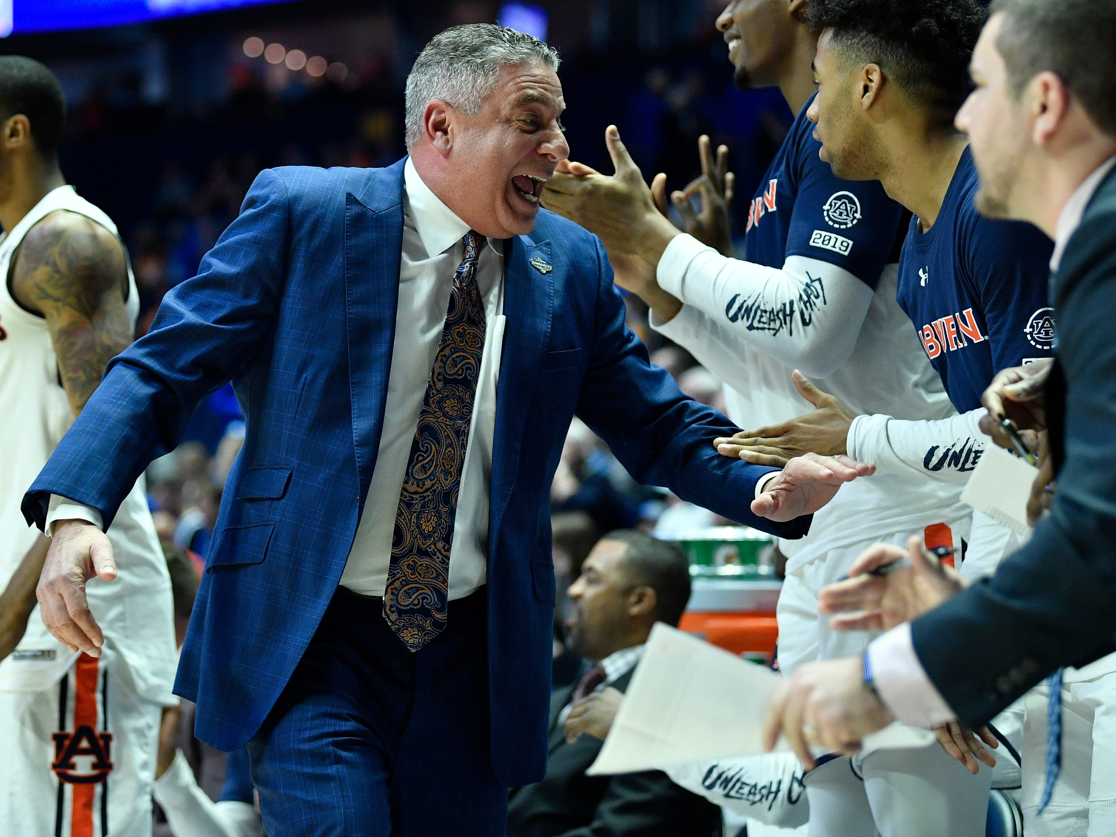 Auburn head coach Bruce Pearl slaps hands during the first half of the SEC Men's Basketball Tournament game against Florida at Bridgestone Arena in Nashville, Tenn., Saturday, March 16, 2019.