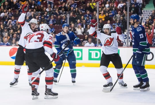 New Jersey Devils' Stefan Noesen (23), Blake Pietila, back left, and Connor Carrick, second from right, celebrate Noesen's goal as Vancouver Canucks' Troy Stecher, third left, and Alexander Edler, right, of Sweden, react during the third period of an NHL hockey game Friday, March 15, 2019, in Vancouver, British Columbia.