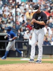Mar 16, 2019; Tampa, FL, USA;New York Yankees pitcher J.A. Happ (34) reacts after giving up a two run home run as Toronto Blue Jays designated hitter Kendrys Morales (8) runs around the bases during the second inning  at George M. Steinbrenner Field.