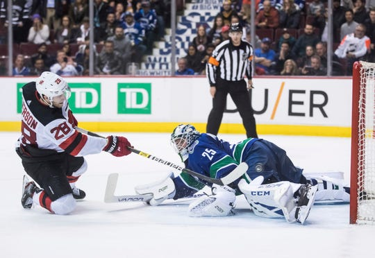 New Jersey Devils' Damon Severson, left, scores against Vancouver Canucks goalie Jacob Markstrom, of Sweden, in the shootout of an NHL hockey game Friday, March 15, 2019, in Vancouver, British Columbia.