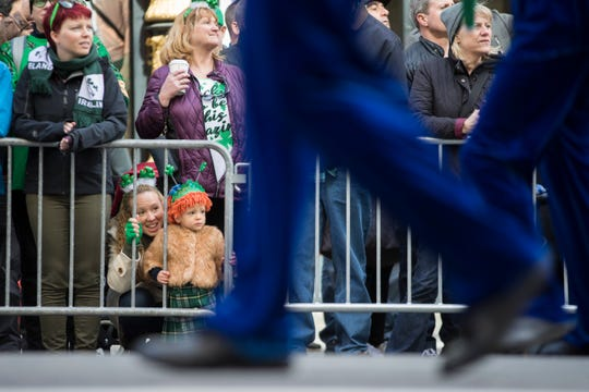Jennifer McCaffrey, bottom left, and daughter Anastasia, 2, watch the participants march up Fifth Avenue during the St. Patrick's Day Parade, Saturday, March 16, 2019, in New York.