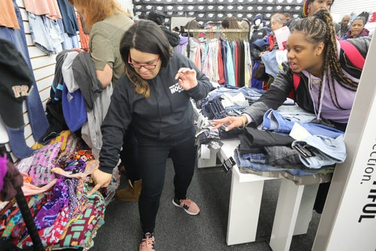 Volunteer, Cynthia Ruiz looks for pants requested by customer Destiny McCartha of Paterson as Destiny does her shopping at the Pop Up Shop.