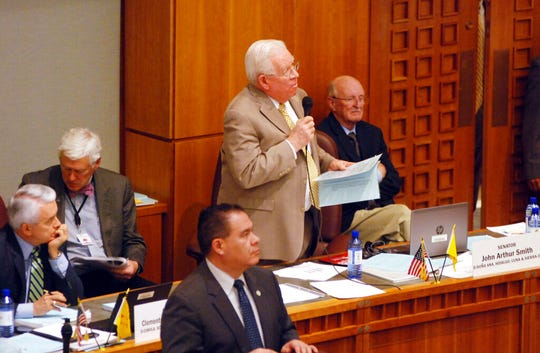 Democratic Sen. John Arthur Smith, of Deming, at center with microphone, guides a $700 million annual spending increase from New Mexico's general fund through approval by the state Senate on Wednesday, March 13, 2019, in Santa Fe, N.M. The House and Senate are moving closer to agreement that would increase spending on public education by nearly half a billion dollars and channel a windfall in tax income toward infrastructure and economic stimulus.