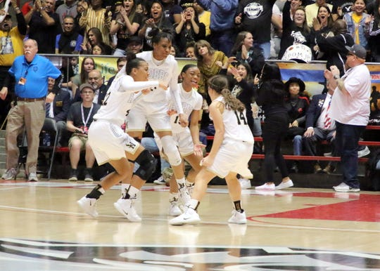 Left to right: Elise Turrubiates, Ayanna Smith and Andrea Evans react to MacKenzye Gibson's (14) 3-pointer as part of an 18-0 run for Hobbs during the first half of Saturday's Class 5A championship game at The Pit in Albuquerque.