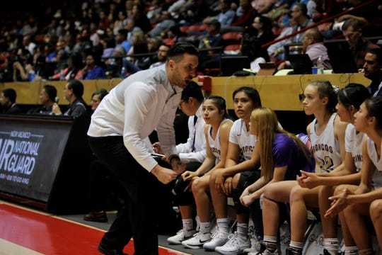 Kirtland Central coach Devon Manning gets his bench pumped up after a foul on Los Lunas during Friday's 4A state championship game at Dreamstyle Arena in Albuquerque.
