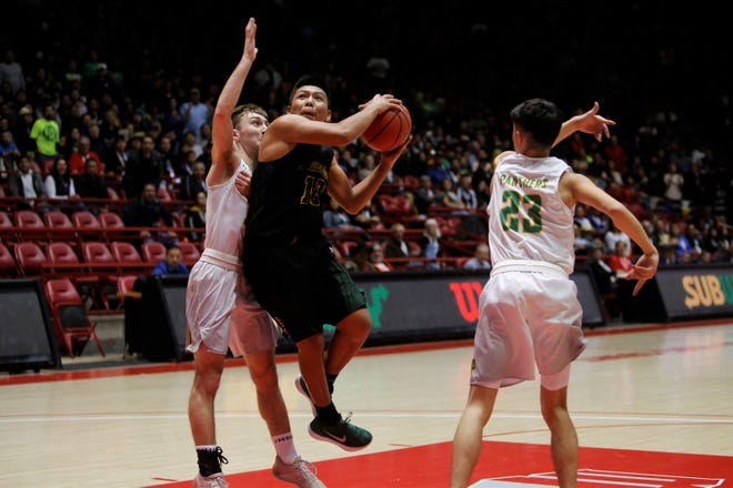 Newcomb's Kelkenny Watchman attacks the basket against Pecos' Anthony Armijo (14) during Saturday's 2A state championship game at Dreamstyle Arena in Albuquerque.