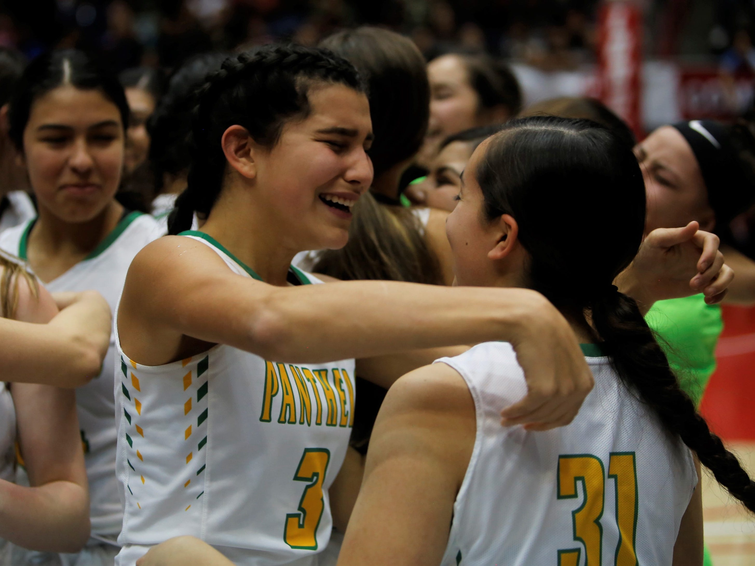 Pecos' MistiDawn Roybal embraces teammate De Anza Dimas after winning Friday's 2A state championship at Dreamstyle Arena in Albuquerque. Pecos defeated Mescalero Apache, 53-46 in overtime.