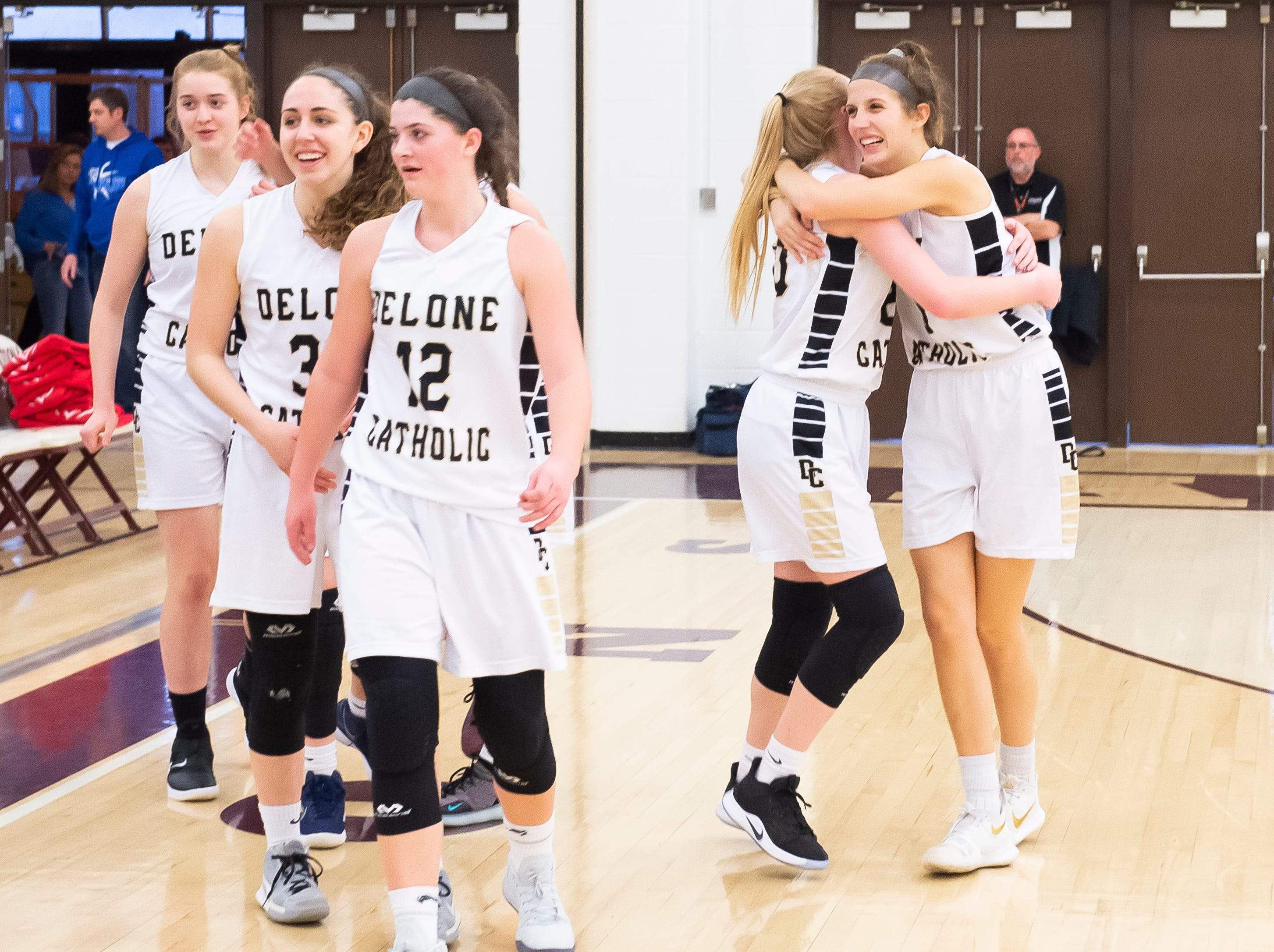 Delone Catholic's Maggie Wells and Brooke Lawyer hug after defeating Neshannock in a PIAA 3A quarterfinal in Altoona, Pa., on Friday, March 15, 2019. The Squirettes won 50-41.