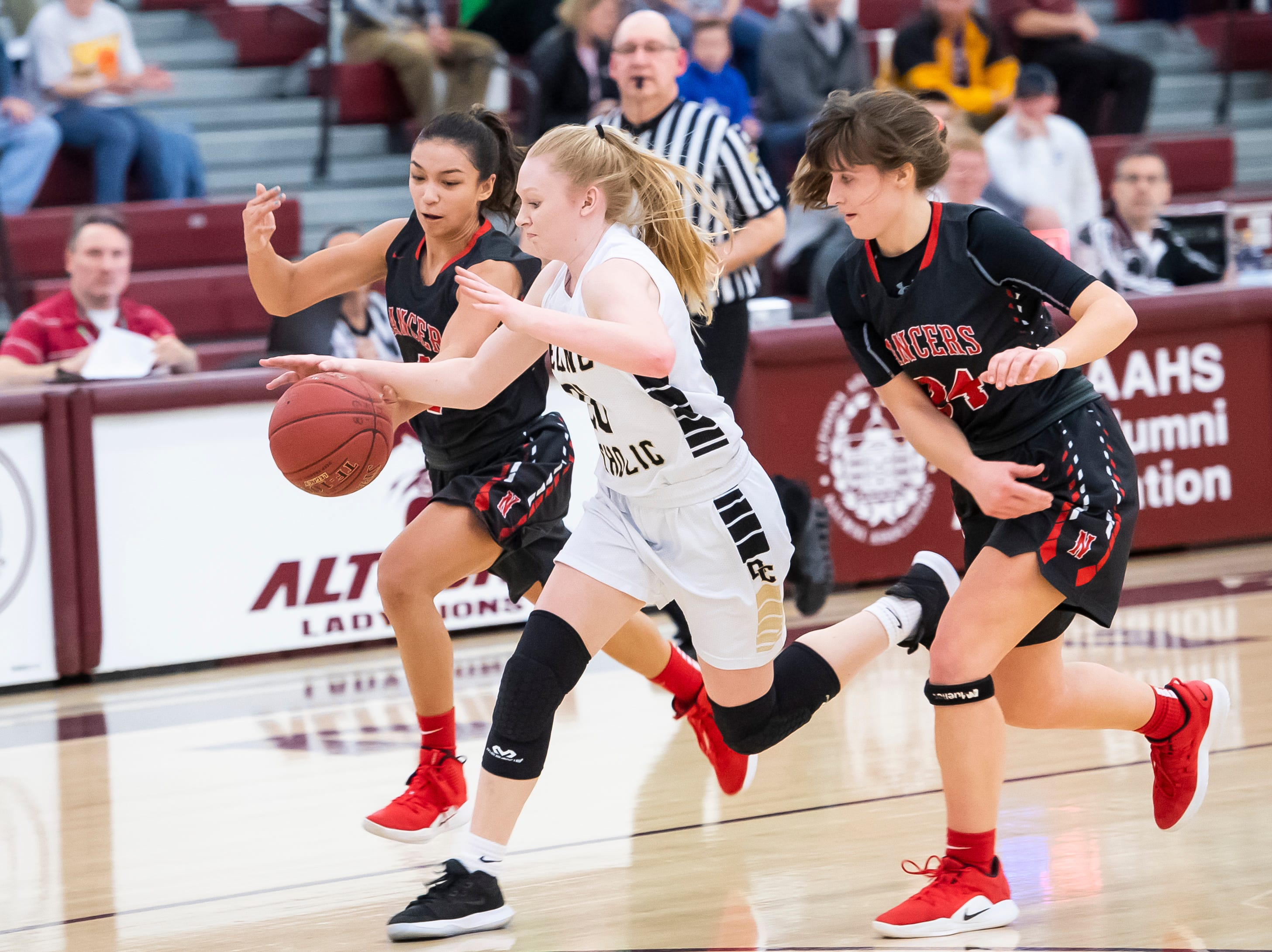 Delone Catholic's Brooke Lawyer dribbles down the court between Neshannock's Neleh Nogay and Brianna Dean to score a layup during a PIAA 3A quarterfinal in Altoona, Pa., on Friday, March 15, 2019. The Squirettes won 50-41.