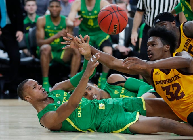 Oregon's Louis King, left, passes around Arizona State's De'Quon Lake during the first half of an NCAA college basketball game in the semifinals of the Pac-12 men's tournament Friday, March 15, 2019, in Las Vegas. (AP Photo/John Locher)