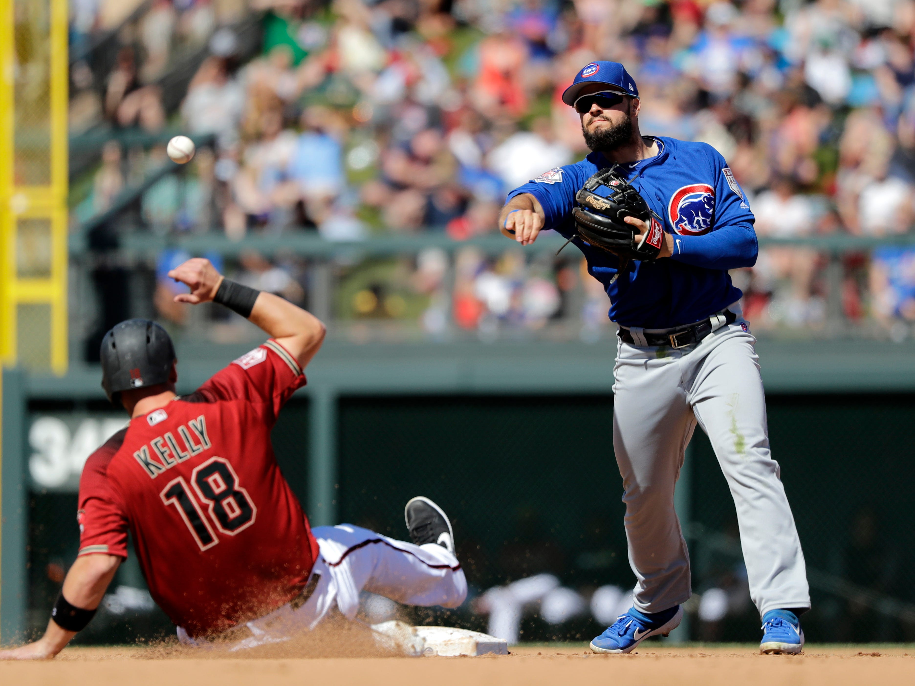 Chicago Cubs second baseman David Bote, right, throws to first base after forcing out Arizona Diamondbacks' Carson Kelly at second base in the fourth inning of a spring training baseball game Saturday, March 16, 2019, in Scottsdale, Ariz. Diamondbacks' Matt Szczur was safe at first on the fielder's choice.