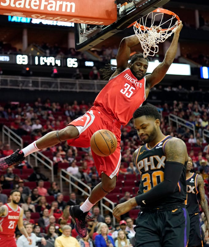 Houston Rockets' Kenneth Faried (35) hangs on the rim after dunking the ball as Phoenix Suns' Troy Daniels (30) avoids him during the second half of an NBA basketball game Friday, March 15, 2019, in Houston. The Rockets won 108-102. (AP Photo/David J. Phillip)