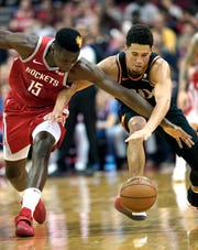 Houston Rockets' Clint Capela (15) and Phoenix Suns' Devin Booker reach for a loose ball during the second half of an NBA basketball game Friday, March 15, 2019, in Houston. The Rockets won 108-102. (AP Photo/David J. Phillip)