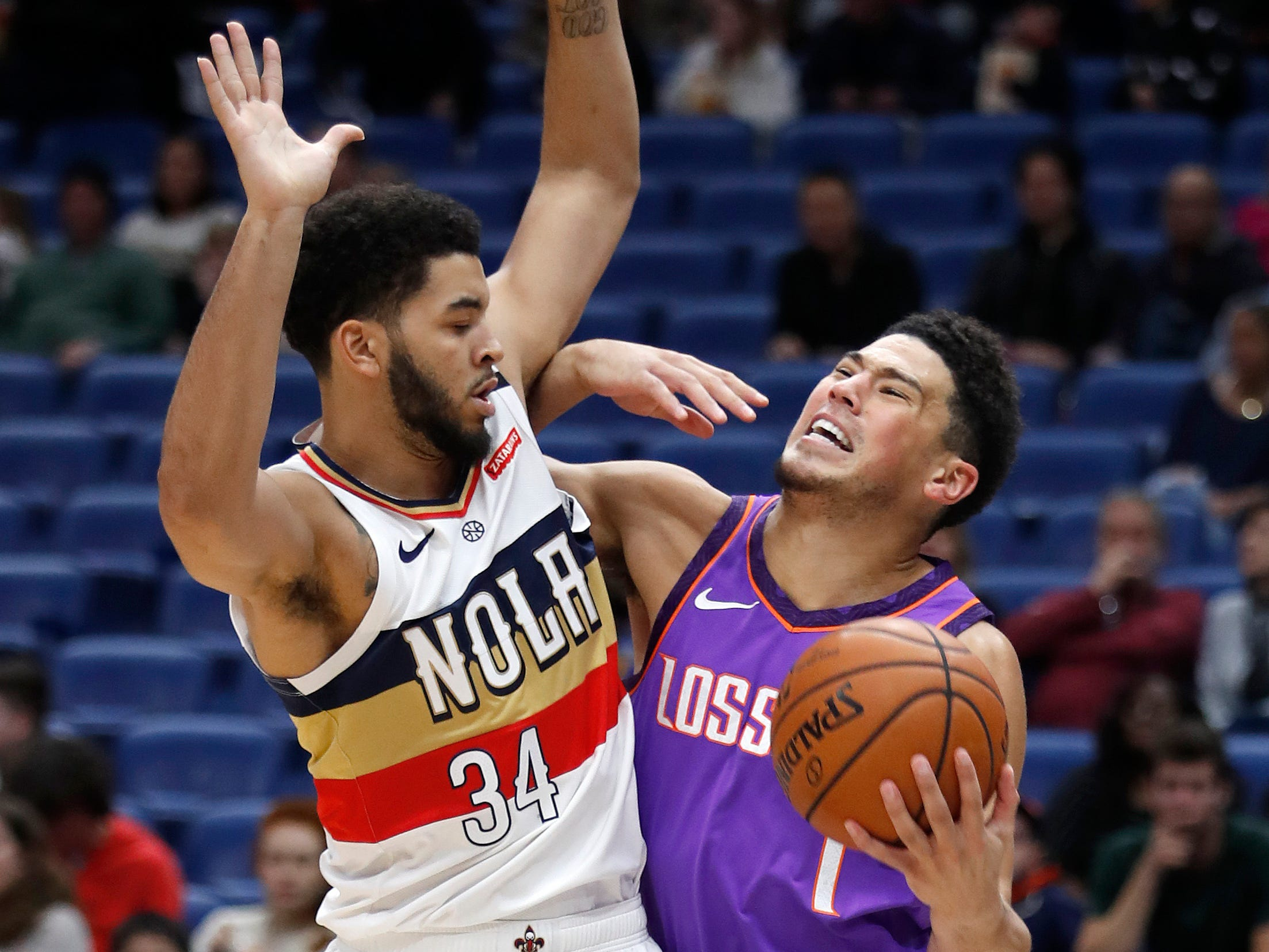Phoenix Suns guard Devin Booker (1) is defended by New Orleans Pelicans guard Kenrich Williams (34) during the first half of an NBA basketball game in New Orleans, Saturday, March 16, 2019.