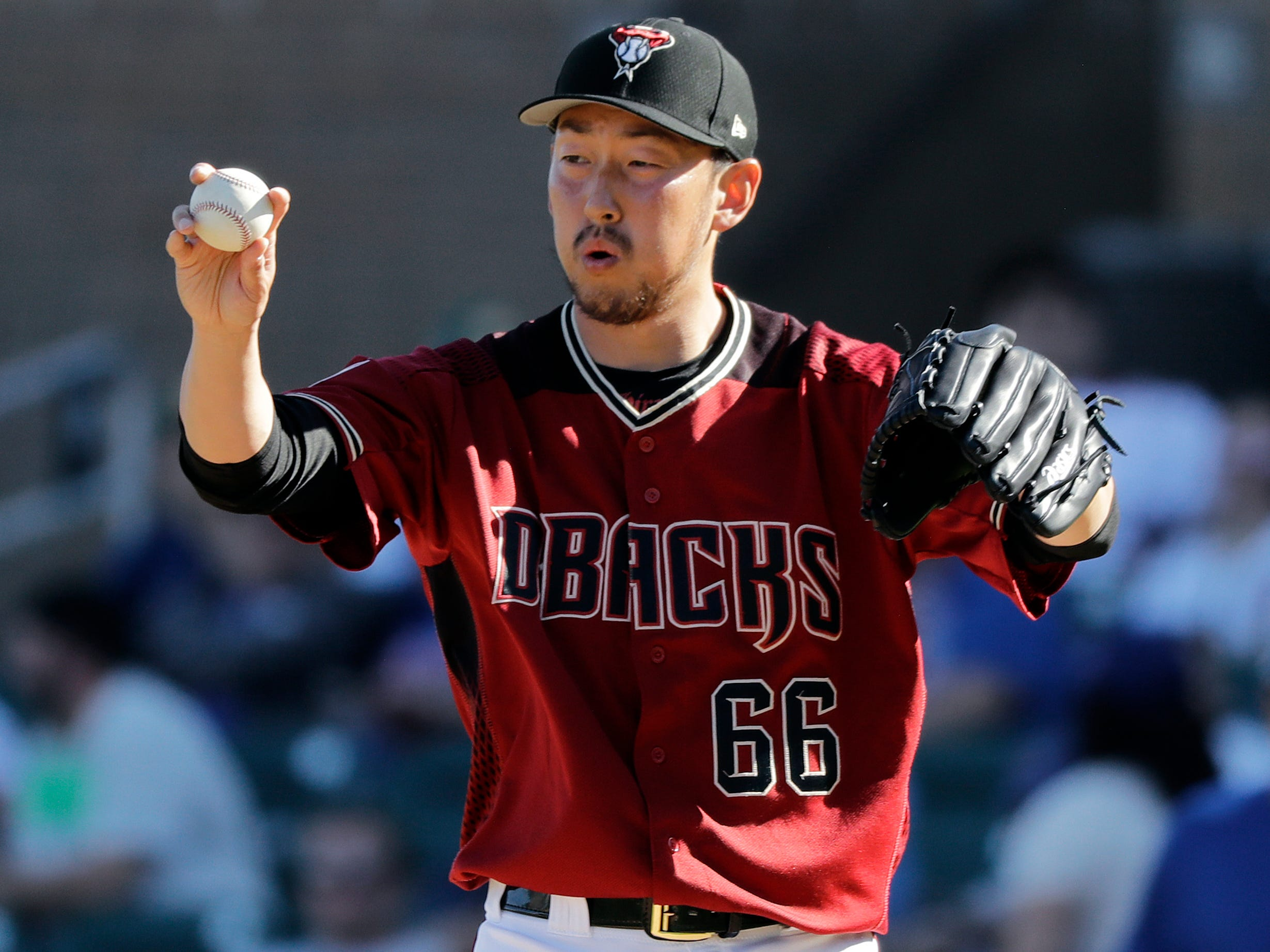 Arizona Diamondbacks' Yoshihisa Hirano stretches between pitches against the Chicago Cubs in the eighth inning of a spring training baseball game Saturday, March 16, 2019, in Scottsdale, Ariz.
