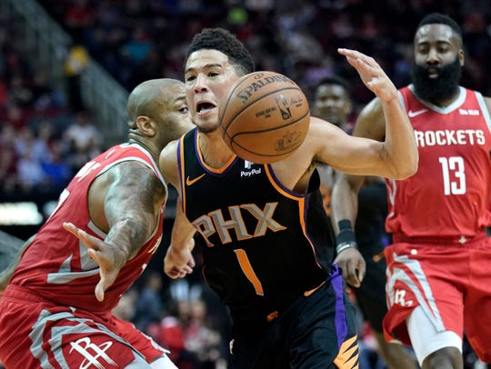 Phoenix Suns' Devin Booker (1) drives past Houston Rockets' PJ Tucker, left, during the first half of an NBA basketball game Friday, March 15, 2019, in Houston. (AP Photo/David J. Phillip)