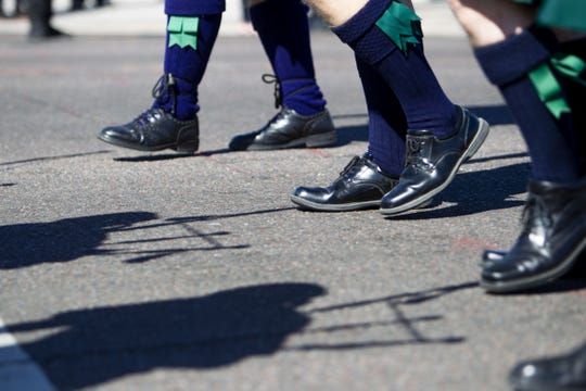 Bagpipe players wear high socks decorated with green ribbons during the Phoenix St. Patrick's Day Parade on March 16, 2019.