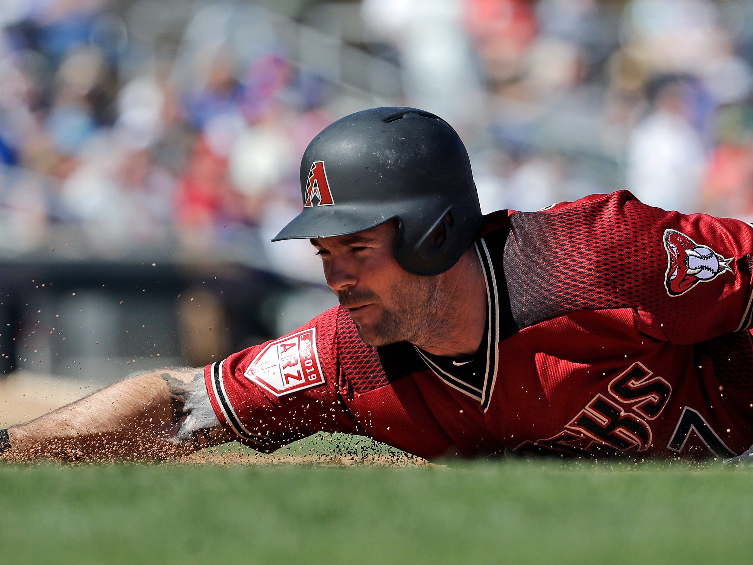 Arizona Diamondbacks' Matt Szczur dives safely back to first base on a pick-off attempt against the Chicago Cubs in the fourth inning of a spring training baseball game Saturday, March 16, 2019, in Scottsdale, Ariz.