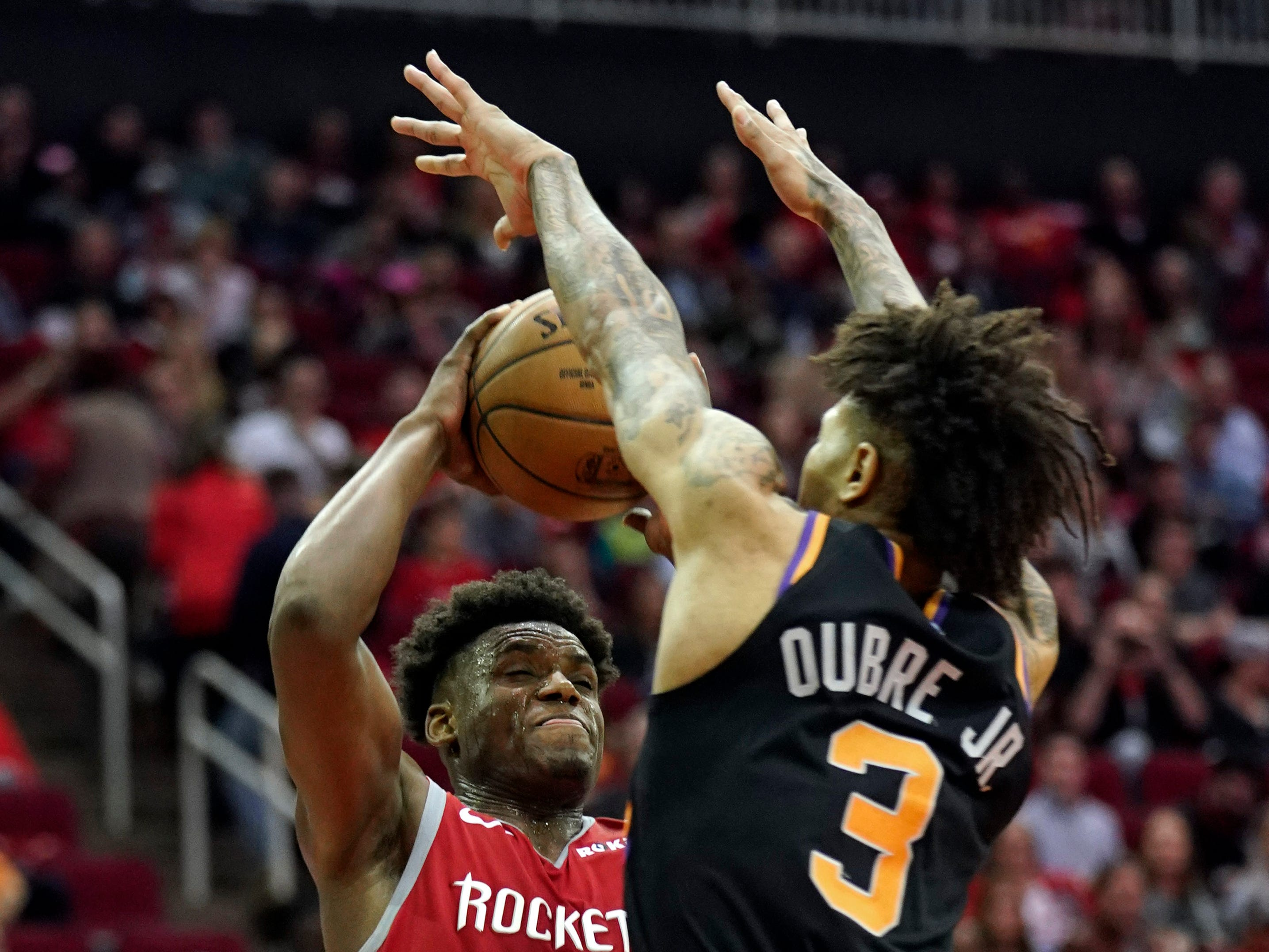 Houston Rockets' Danuel House Jr. (4) shoots as Phoenix Suns' Kelly Oubre Jr. (3) defends during the second half of an NBA basketball game Friday, March 15, 2019, in Houston. The Rockets won 108-102. (AP Photo/David J. Phillip)