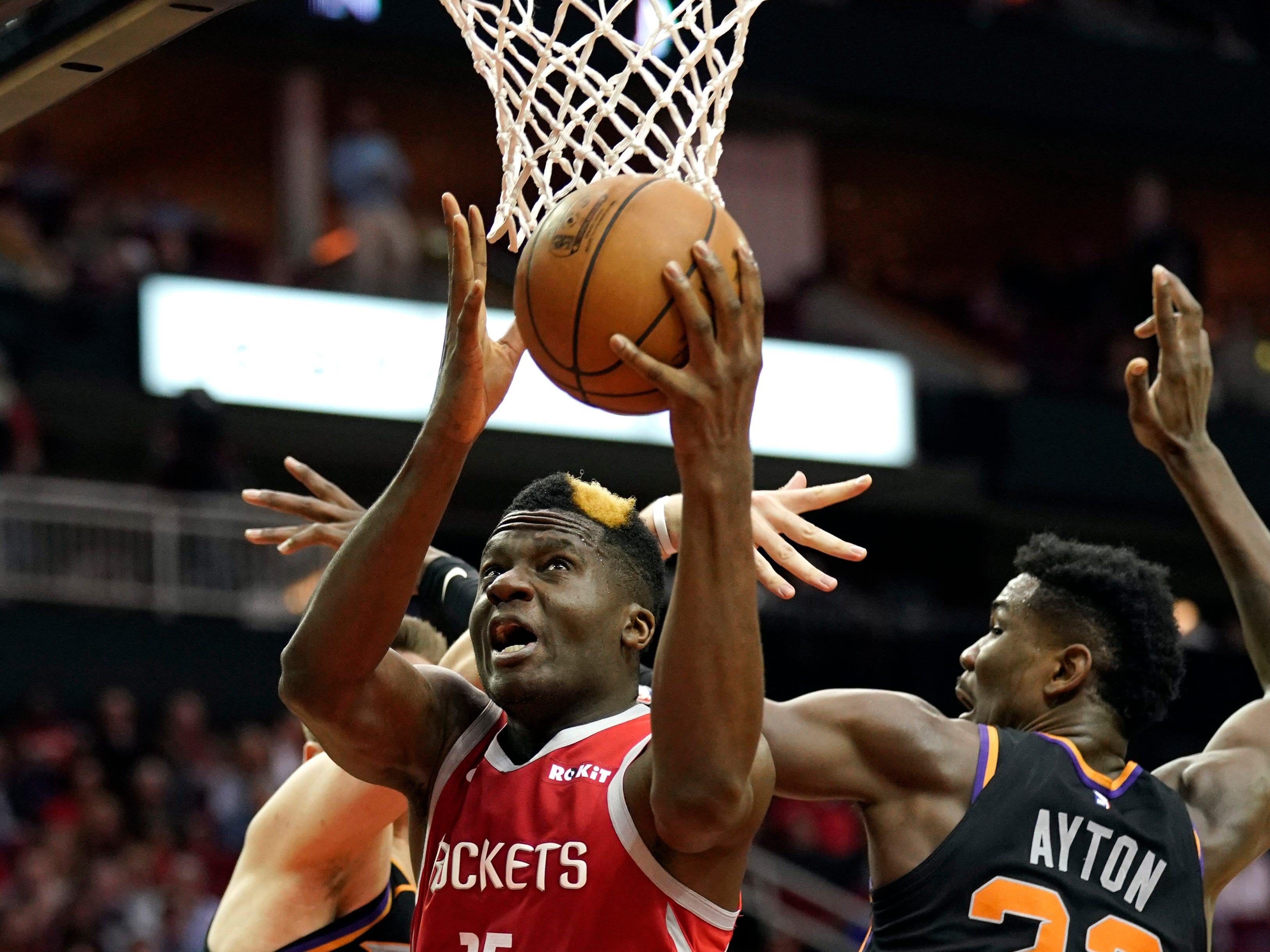Houston Rockets' Clint Capela (15) goes up for a shot as Phoenix Suns' Deandre Ayton (22) and Dragan Bender defend during the second half of an NBA basketball game Friday, March 15, 2019, in Houston. The Rockets won 108-102. (AP Photo/David J. Phillip)