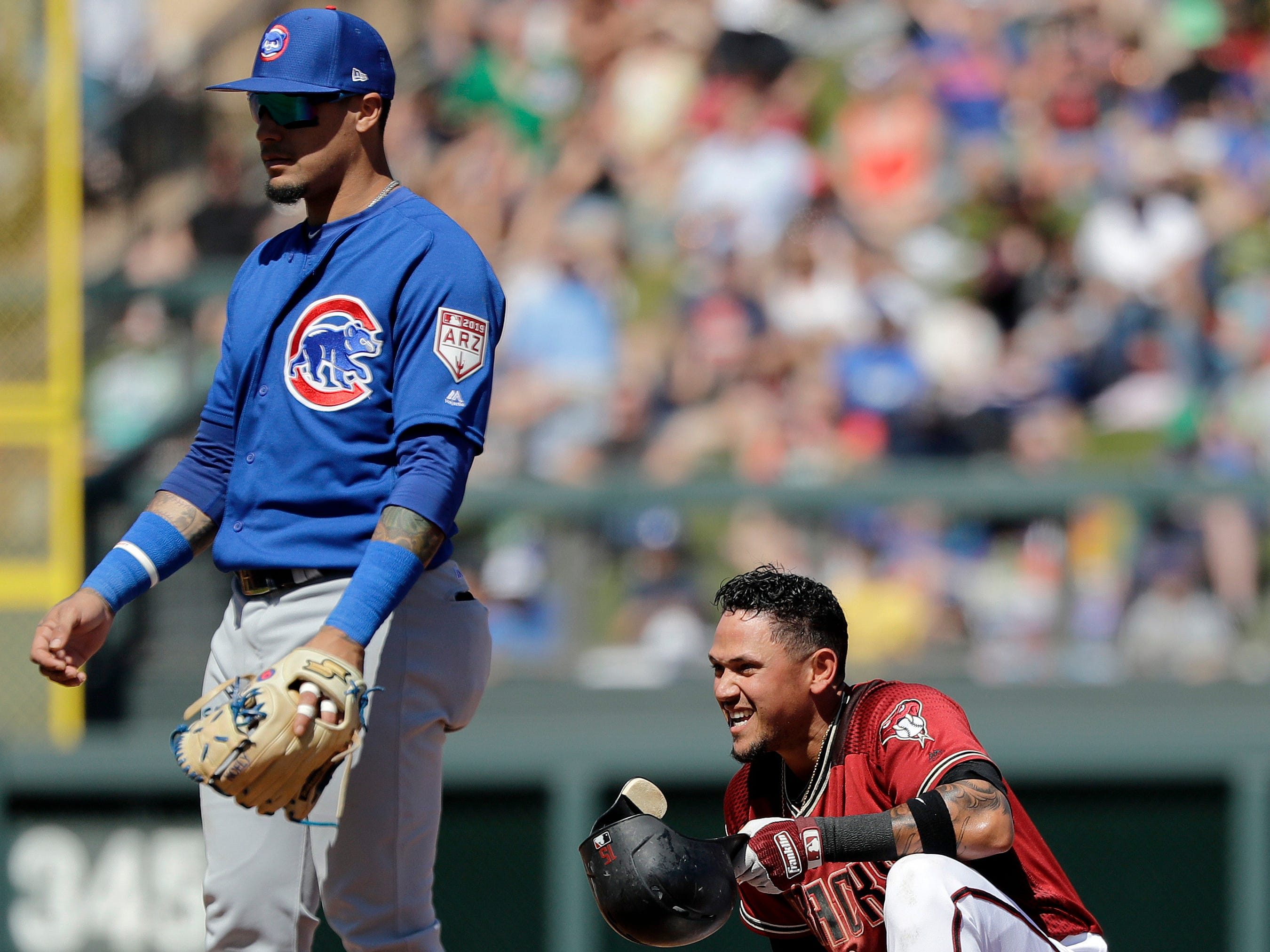 Arizona Diamondbacks' Ildemaro Vargas, right, smiles after arriving safely at second base on his double as Chicago Cubs shortstop Javier Baez stands nearby in the third inning of a spring training baseball game Saturday, March 16, 2019, in Scottsdale, Ariz.