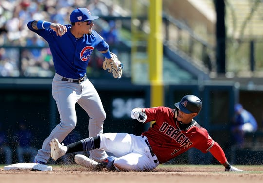 Chicago Cubs shortstop Javier Baez, left, throws to first base after forcing out Arizona Diamondbacks' Ketel Marte at second base in the first inning of a spring training baseball game Saturday, March 16, 2019, in Scottsdale, Ariz. Baez completed the double play on Diamondbacks' Carson Kelly at first.