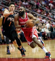 Houston Rockets' James Harden (13) drives toward the basket as Phoenix Suns' Devin Booker (1) defends during the second half of an NBA basketball game Friday, March 15, 2019, in Houston. The Rockets won 108-102. (AP Photo/David J. Phillip)