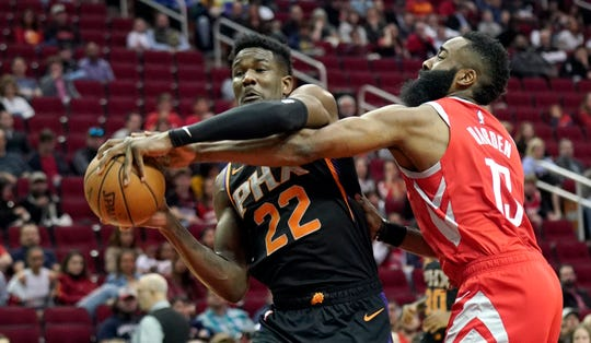Houston Rockets' James Harden (13) tries to steal the ball from Phoenix Suns' Deandre Ayton (22) during the first half of an NBA basketball game Friday, March 15, 2019, in Houston. (AP Photo/David J. Phillip)