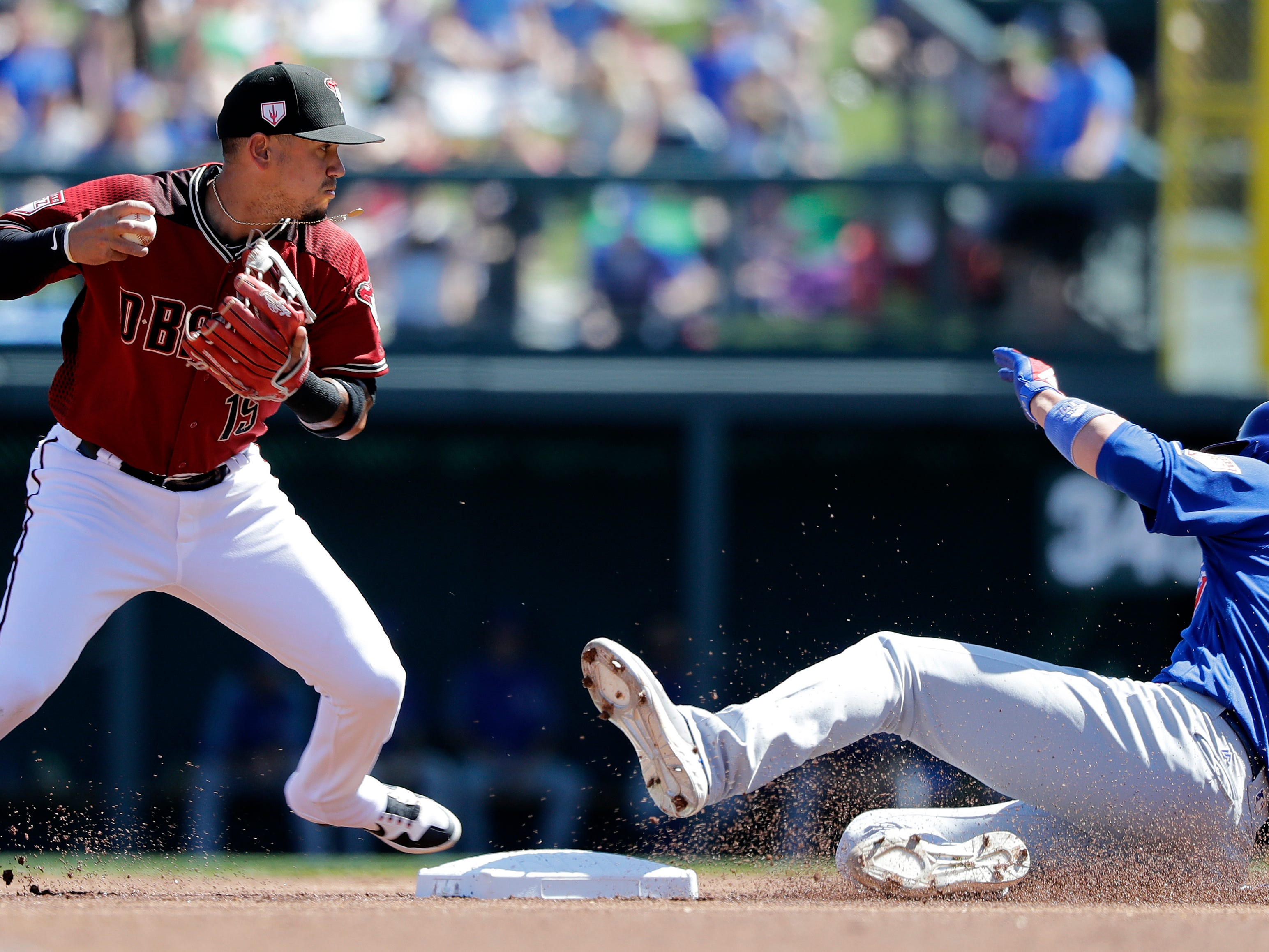 Arizona Diamondbacks third baseman Ildemaro Vargas, left, moves toward second base to tag it and force out Chicago Cubs' Kris Bryant (17) before throwing to first base in the first inning of a spring training baseball game Saturday, March 16, 2019, in Scottsdale, Ariz. Cubs' Anthony Rizzo was tagged out on a rundown between first and second base on the play.