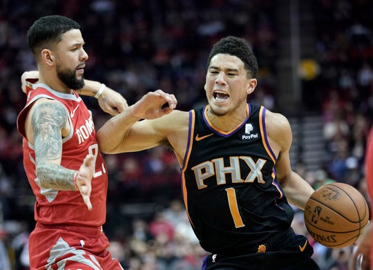 Phoenix Suns' Devin Booker (1) pushes off against Houston Rockets' Austin Rivers during the first half of an NBA basketball game Friday, March 15, 2019, in Houston. (AP Photo/David J. Phillip)