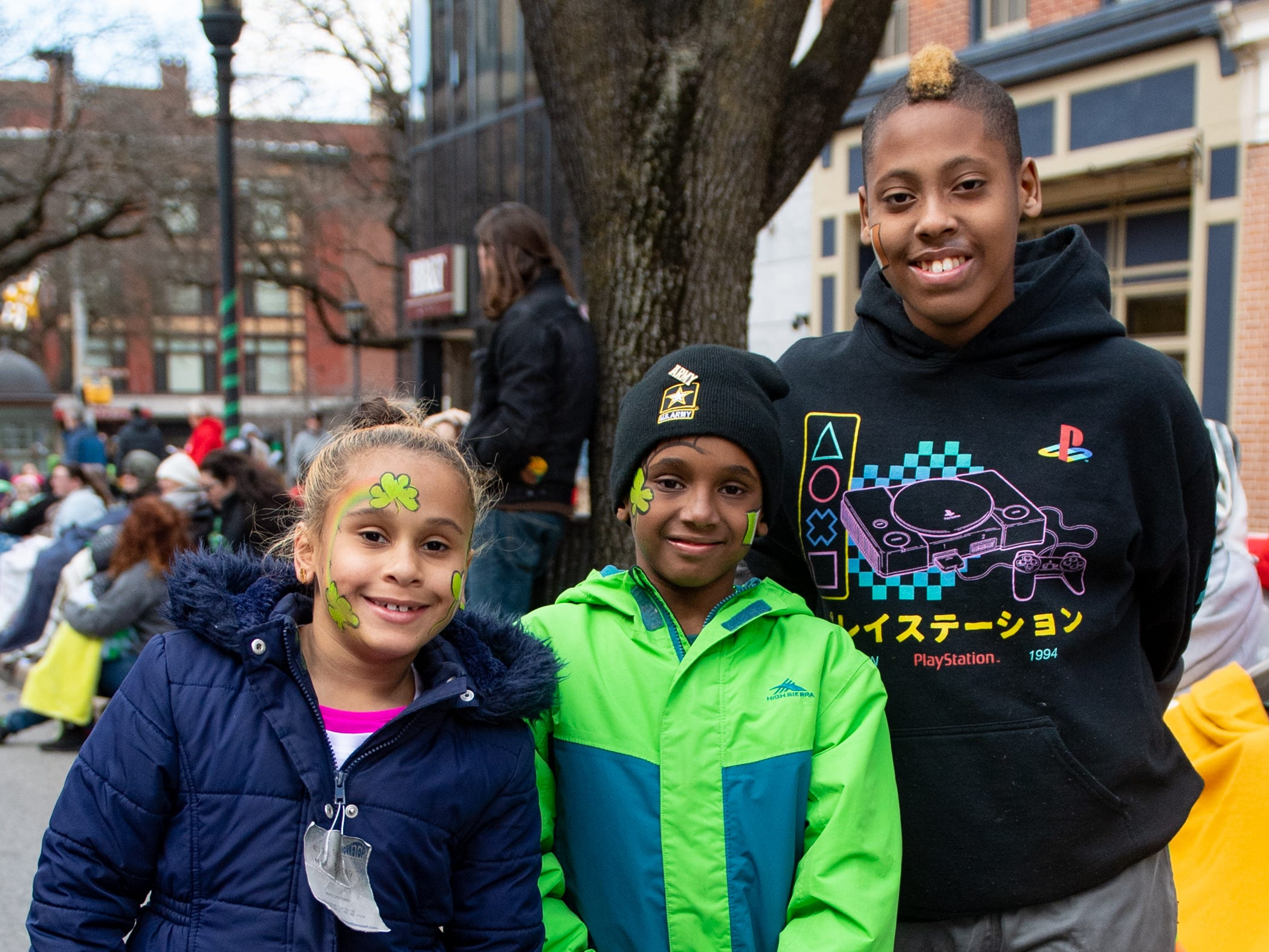 (Left to right) Apple, Dominick and Cain Dowell have paintings of shamrocks on their faces for the parade, March 16, 2019.