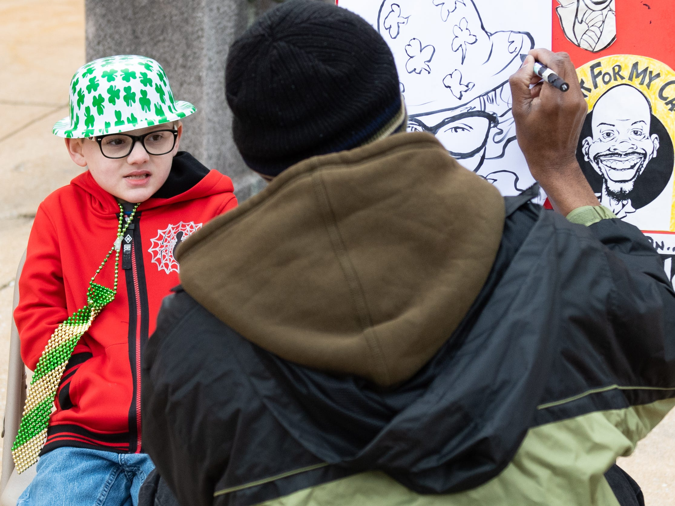 Max Sheffer of Windsor Township gets a caricature done during the St. Patrick's Day Parade, March 16, 2019.