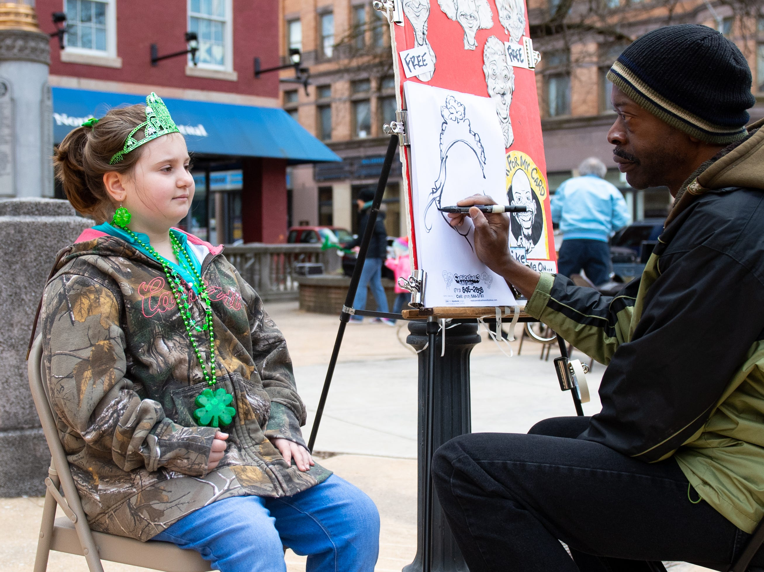 Artist Mel Conrad draws Jaylee Biller during the 2019 St. Patrick's Day Parade, March 16, 2019.
