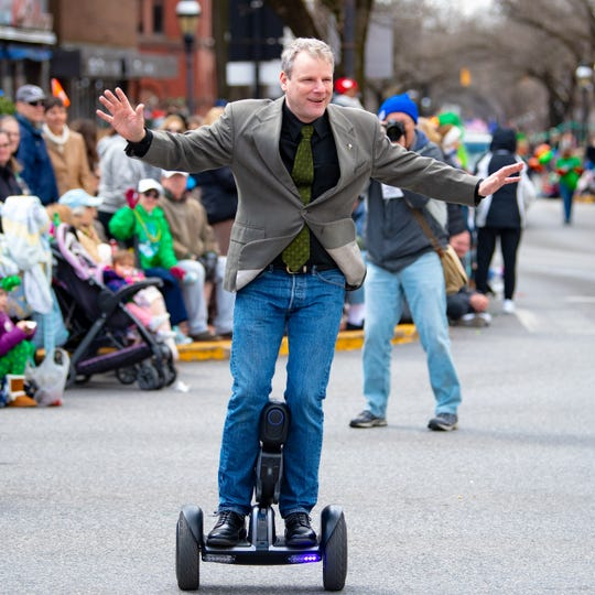 Mayor Michael Helfrich glides by on a hover-board during the 36th Annual St. Patrick's Day Parade, March 16, 2019.