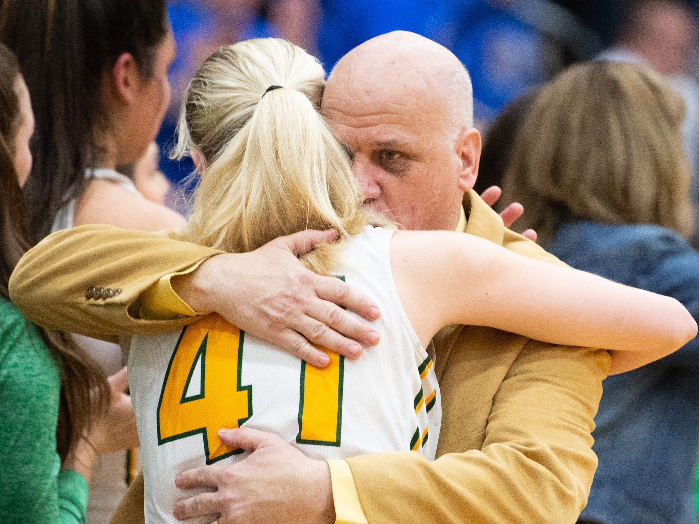 York Catholic Head Coach Kevin Bankos hugs Elena Kondrasuk (41) as the game comes to a close, March 15, 2019 at Mifflin County High School. The Fighting Irish lost to the Lady Blue Devils 53 to 47.