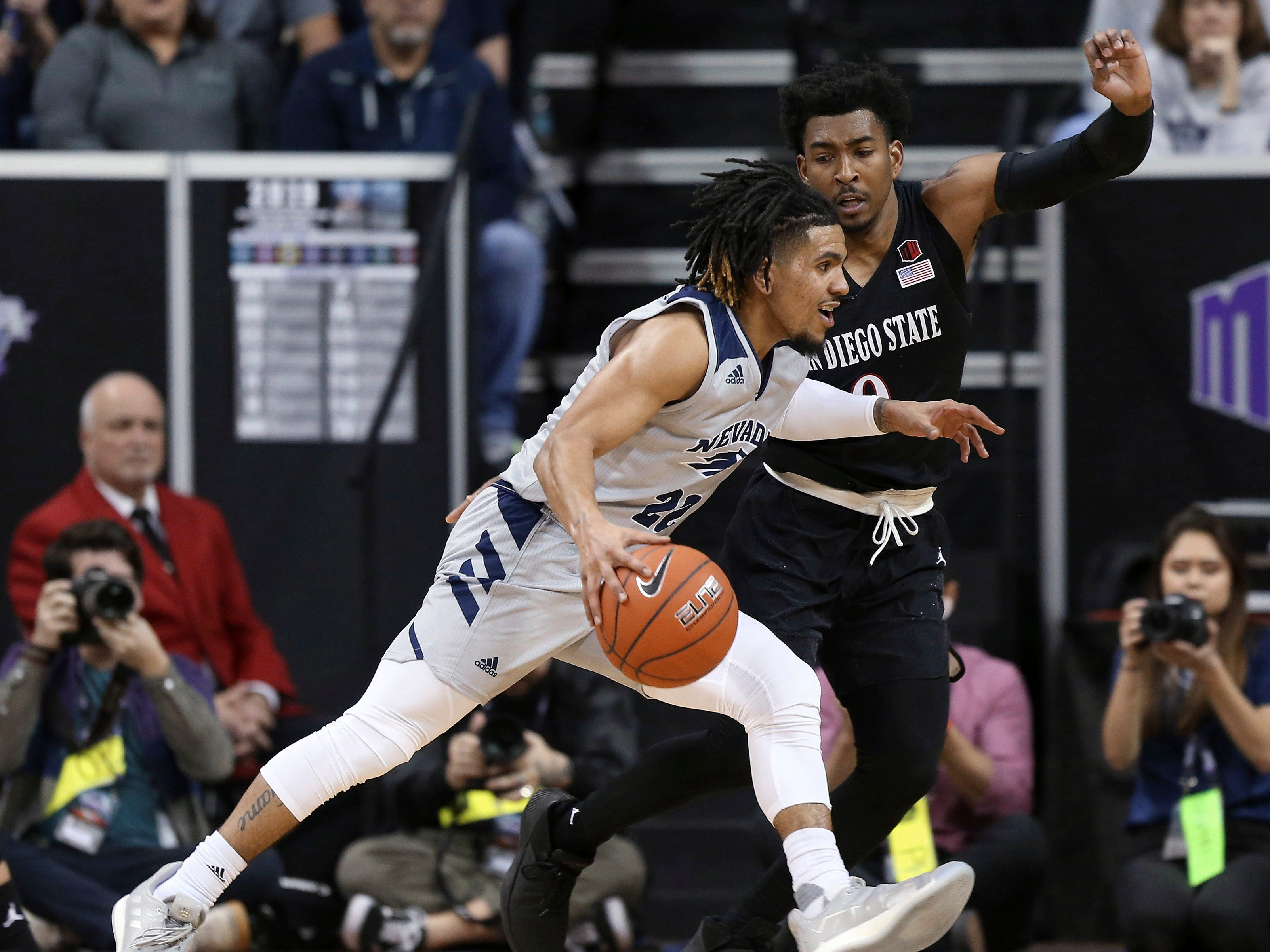 San Diego State's Devin Watson (0) defends as Nevada's Jazz Johnson (22) drives during the second half of an NCAA college basketball game in the Mountain West Conference men's tournament Friday, March 15, 2019, in Las Vegas. (AP Photo/Isaac Brekken)